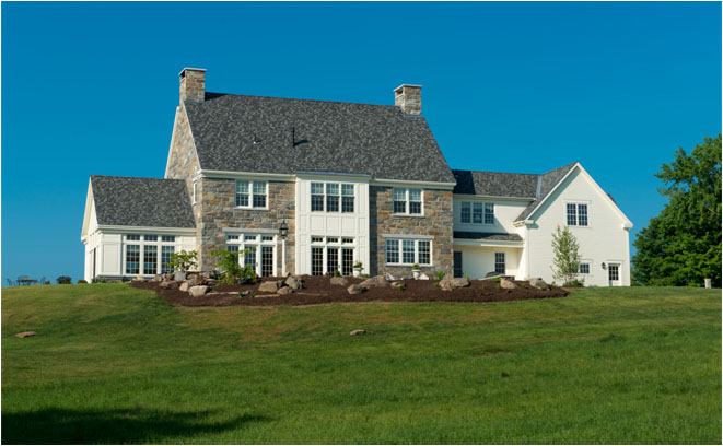 Hilltop home in Salisbury NH incorporating stone construction with a sunroom overlooking the mountains
